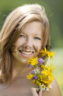 Lachende junge Frau mit Blumen in der Hand
