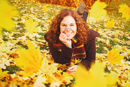 Young woman lying on a lawn surrounded by falling autumn leaves. Fall, seasonal and autumnal concept.