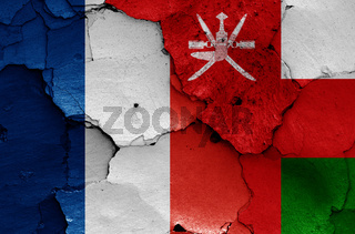 flags of France and Oman painted on cracked wall