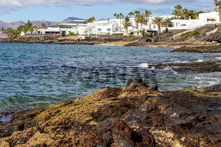 Rocky coast of Puerto del Carmen at Canary island Lanzarote with lava rocks and blue water in the foreground, white houses, palm trees and volcanic mountain range in the background