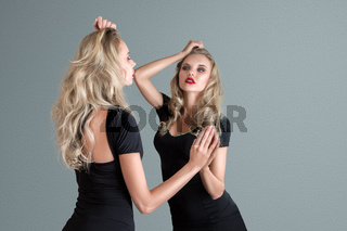Young woman looking in mirror