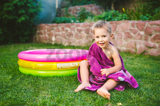Summer vacation theme. A small 3 year old Caucasian boy playing in the backyard of a house on the grass near a round inflatable colored pool wrapped up, wiped to be a dry towel in red swimming trunks