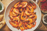 Traditional fried tiger prawn with garlic bread as top view served in a white frying pan