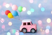 Kleines rosa Auto mit Luftballons