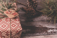 Christmas present rustic gift wrapped with natural vintage twine on old wood floor with copyspace