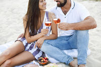 Couple drinking rose wine at picnic on the beach