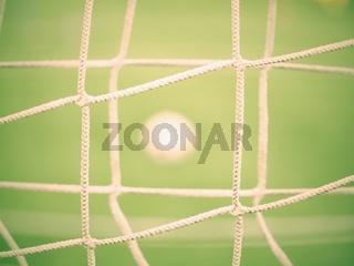 View through football gate net. Soccer ball on green grass