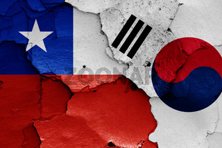 flags of Chile and South Korea painted on cracked wall