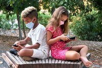 Multiracial kids using modern gadgets sitting outdoors
