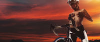 Panoramic bright sunset cloudy sky, naked cyclist sexy slim woman topless cover breast with hands pose standing on bike wearing activewear helmet posing outdoors. Beauty, lifestyle concept, copy space