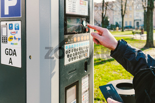 man pays for parking with a credit card with NFS technology. Easy payment. Process of paying in machine parking terminal. Payment for parking in the City of Gdansk, Poland February 8, 2020