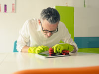 Middle-aged man thoroughly cleans a white dining room table