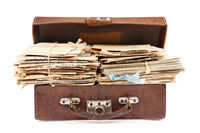 Bunches of old paper mails in suitcase isolated on white