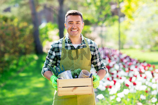 happy man with tools in box at summer garden