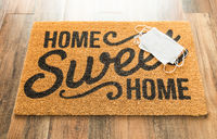Several Medical Face Mask Rests on Home Sweet Home Welcome Mat Amidst The Coronavirus Pandemic