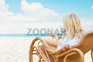 Young beautiful blonde woman enjoying tea with tropical sea view while sitting on chair at luxury resort lounge