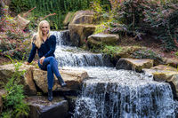 A Lovely Blonde Model Poses Outdoors Near A Waterfall At A Local Park