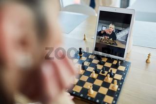Frau spielt Schach mit einer Freundin im Videochat