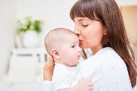 Mutter gibt Baby Kuss auf die Stirn