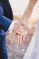 Groom holds bride hand in white dress. Blurred background