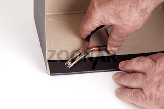 Man pulling with pliers screw on the box of fixed