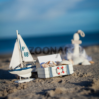 sailing boat and seashell in sand decoration closeup