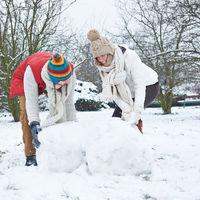 Mann und Frau bauen Schneemann im Winter