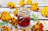 Alcohol tincture of marigolds in jar on wooden board