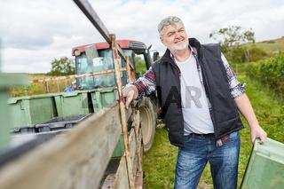 Weinbauer am Traktor mit den Erntekisten