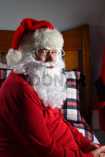 Closeup of  Santa Claus sitting on his bed in his red long johns, ready for sleep after Christmas.
