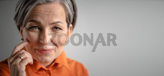 Charming gray-haired woman smiles touching cheek with finger. Selective focus on female face with tiny wrinkles. Close up portrait. Mature skin care concept. Horizontal blank witn copy spase for text