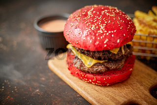 Homemade red sesame bun double bacon cheese burger. Served with french fries on wooden board.