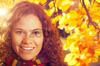 Pretty young woman smiling surrounded by yellow and orange autumnal leaves. Fall and seasons concept.
