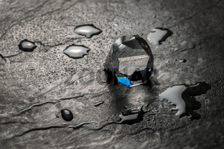 Crystal on wet slate with blue reflex