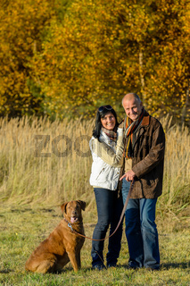Couple with dog in park autumn sunset
