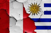 flags of Peru and Uruguay painted on cracked wall