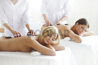 Friends getting hot stone massage