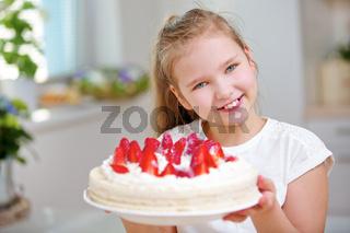 Kind hält Erdbeertorte mit frischen Erdbeeren