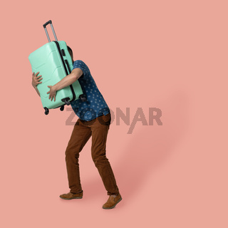 Man hugs a suitcase holding it in front of himself while posing on colored background. Caucasian man in a t-shirt and brown trousers goes on trip. Vacation concept