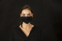 Studio portrait of a young woman wearing a face mask on dark background.