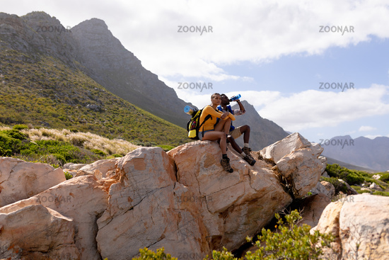 Fit afrcan american couple wearing backpack resting drinking water on the coast