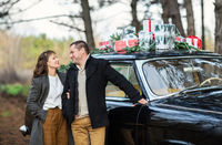 Couple kissing in vintage car with presents on roof