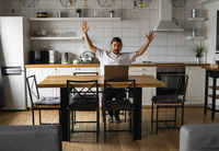 Excited businessman feeling happy about successful project. Man holding hands in the air and looking at laptop while sitting on a kitchen at home. Happy freelancer, student working at laptop at home.