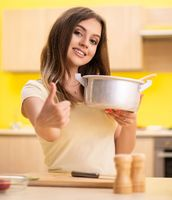 Young woman cooking soup in kitchen at home