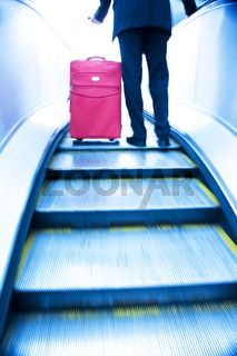 Businessman travelling up an escalater