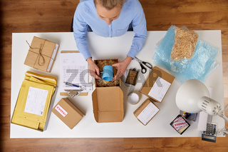 woman packing mug to parcel box at post office