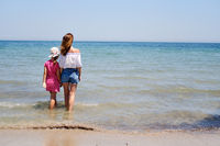 Back view mother and little daughter holding hands standing in sea water looking into horizon, copy space for text. Family travel and summer vacation concept