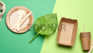 disposable paper utensils from brown craft paper and recycled materials on a green background