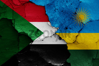 flags of Sudan and Rwanda painted on cracked wall