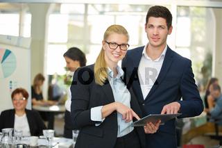 Mann und Frau arbeiten mit Tablet Computer